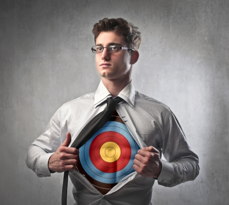Young businessman showing a target on his chest under his shirt Stock Photo