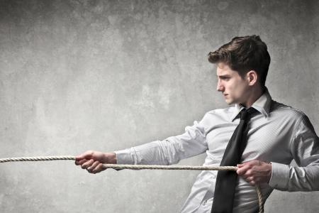 tug o war: Joven hombre de negocios tirando de una cuerda Foto de archivo