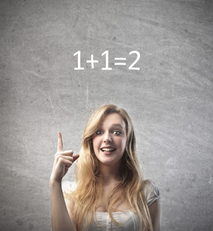 unintelligent: Smiling young woman finding the solution to an easy calculation Stock Photo
