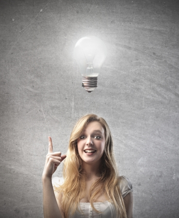 superficial: Smiling young woman having an idea with light bulb over her head