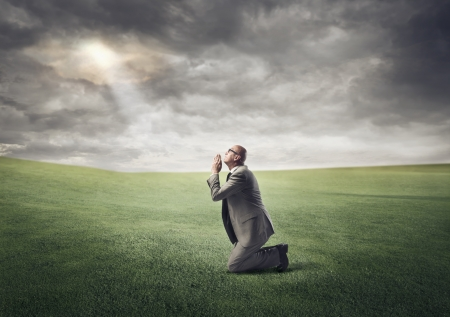 Businessman kneeling on a green meadow and praying photo