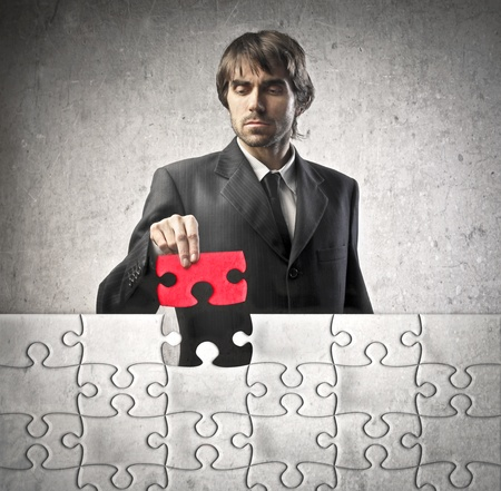 puzzles: Young businessman finishing a puzzle