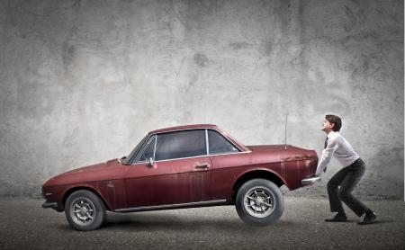 auto old: Hombre de negocios levantando un coche viejo