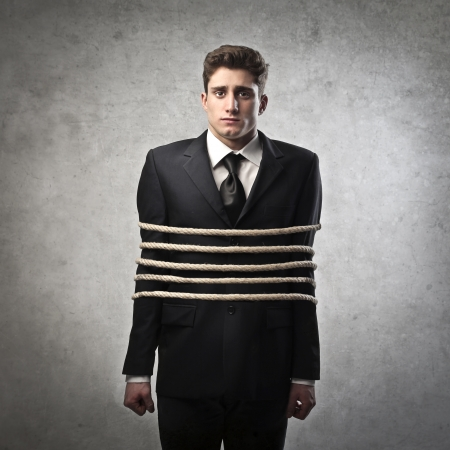 Sad young businessman tied tight with ropes photo