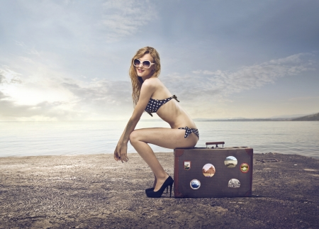 Beautiful young woman in bikini sitting on a suitcase at the beach photo