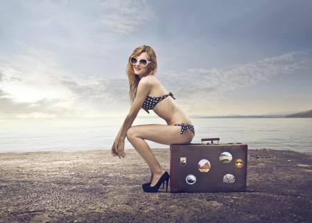 mujer con maleta: Joven y bella mujer en bikini sentada en una maleta en la playa