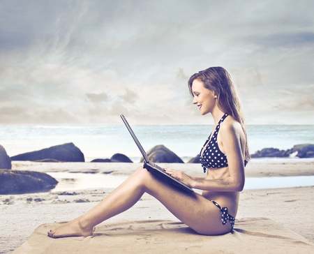 Smiling beautiful woman sitting on a beach and using a laptop photo