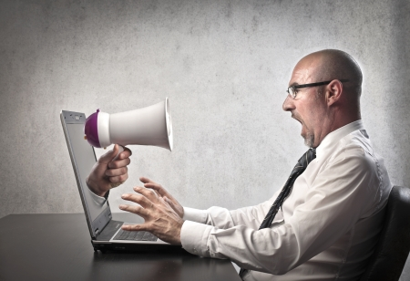 poking: Businessman astonished by a megaphone poking out of his laptop screen