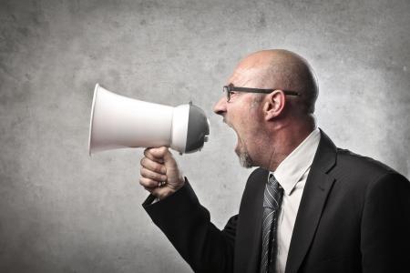 Businessman screaming into a megaphone Stock Photo