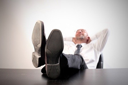 feet on desk: Businessman relaxing on an office chair with his feet on the table