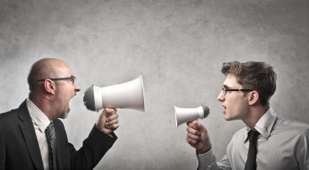 a communication: Businessman screaming into a megaphone against a younger businessman holding a smaller megaphone