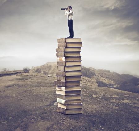 fernrohr: Junger Geschäftsmann, der auf einem Stapel Bücher und mit Hilfe eines Teleskops