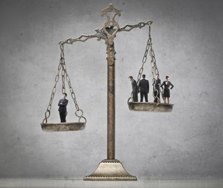 balanza en equilibrio: Ponderación de negocios joven que más de cuatro personas de negocios de otros Foto de archivo