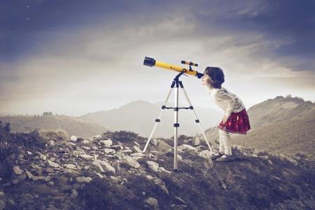 fernrohr: Kleines Mädchen sucht in einem Fernrohr auf einem Hügel Lizenzfreie Bilder