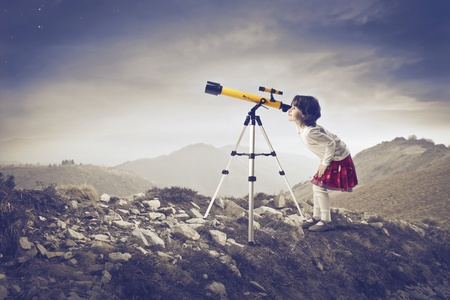 telescopes: Little girl looking into a telescope on a hill Stock Photo