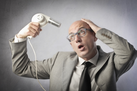 phon: Bald businessman using a hairdryer Stock Photo