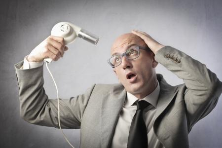 Bald businessman using a hairdryer
