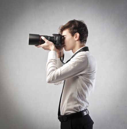 Young businessman taking pictures with a reflex camera Stock Photo