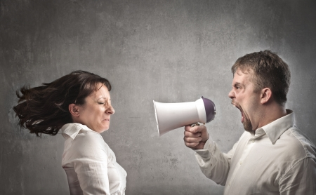 Angry man screaming into a megaphone against his girlfriend photo
