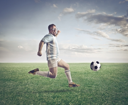 Soccer player running after a football on a football court photo