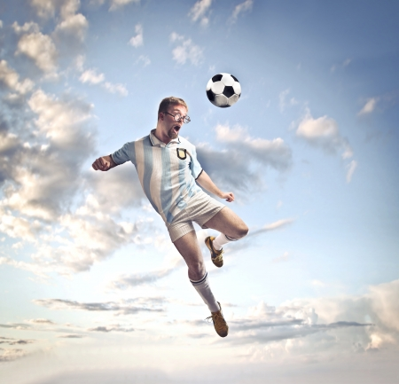 unfit: Soccer player head-shooting a football Stock Photo