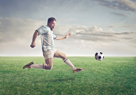 soccer match: Soccer player running after a football on a meadow Stock Photo