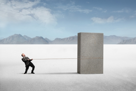 impossible: Businessman pulling a heavy stone block in a desert