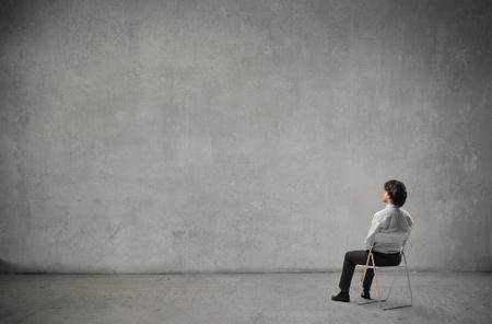back views: Businessman admiring a white wall Stock Photo