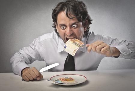 avid: Businessman eating his earning Stock Photo