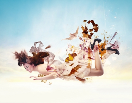 flying woman: woman dressed in feathers and birds flying Stock Photo
