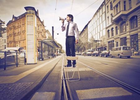 Hombre de negocios hablando a través de un megáfono en la calle