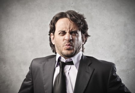 stink: ortrait of businessman disgusted on a gray background Stock Photo