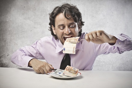 greedy: Businessman eating his earning Stock Photo