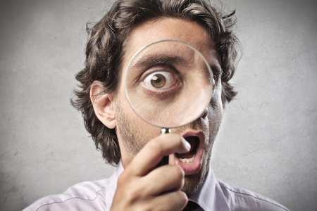 eye lens: Businessman watching through a magnifying glass