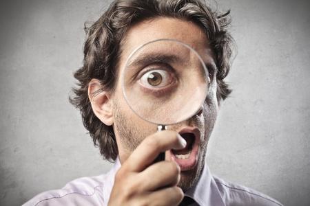 Hombre de negocios mirando a través de una lupa Foto de archivo