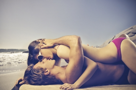 pareja desnuda: Young Lovers Kissing on the Beach