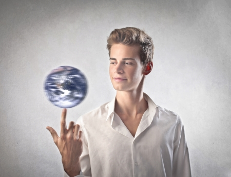 Boy making the world go on on his index finger