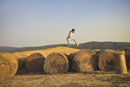 ni�o saltando: Pa�s muchacho que salta de una hilera de gavillas