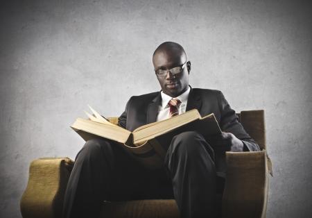 Black businessman reading a big book photo