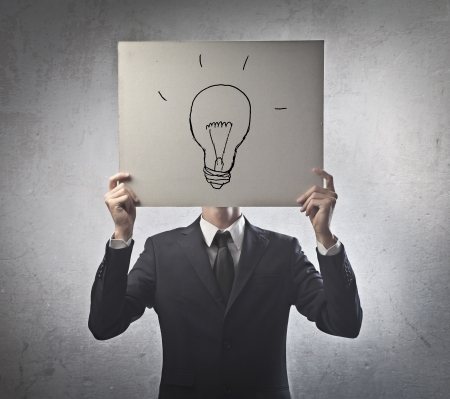 Businessman has instead of the face a cardboard on which is drawn a lamp Stock Photo - 15127539