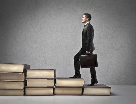 Businessman climbing a ladder of books photo