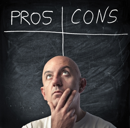 cons: Man reflecting on the pros and the cons of a choice Stock Photo