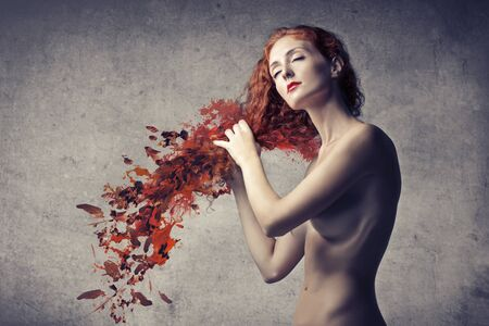 Beautiful woman caressing her red hair that turn into red leaves Stock Photo - 15137883
