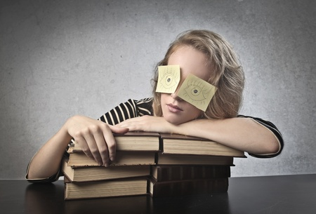 tedium: Blonde girl on her books with two post-it on her eyes Stock Photo