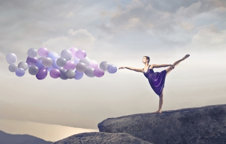 Blonde dancer stepping on a cliff holding some ballons photo
