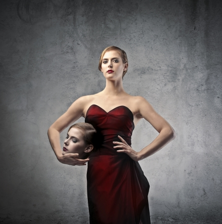 beheading: Elegant blonde woman with her face under her arm Stock Photo