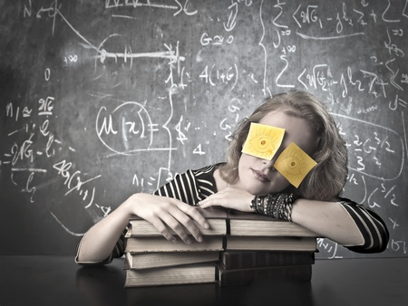 Black and white blonde girl sleeping on her books with two post-it on her eyes photo