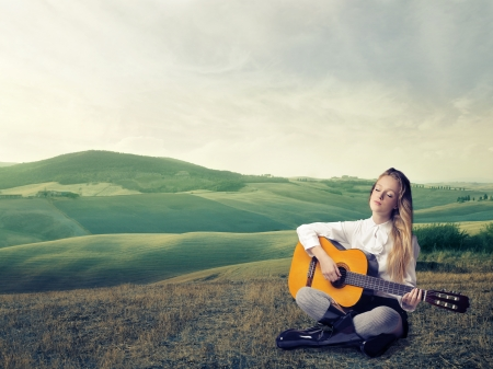 Woman beat guitar: Blonde girl playing the guitar in a large grace field