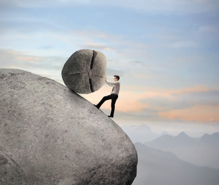 stone work: Businessman pushing a boulder on a rock