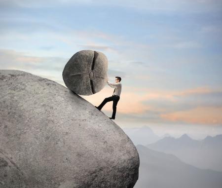 disco duro: Hombre de negocios empujando una roca sobre una roca